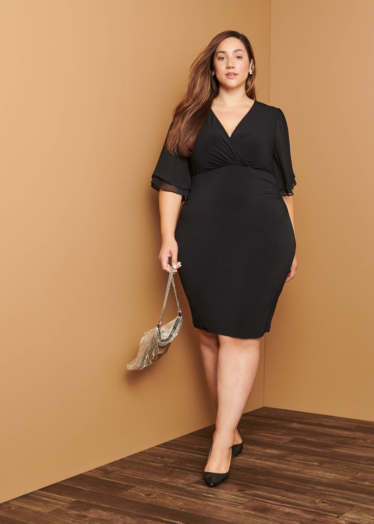plus size woman in black bat wing sleeve cocktail dress on day to night connected apparel blog