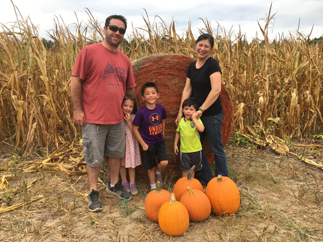 The Mckelvy family posed together in a pumpkin patch