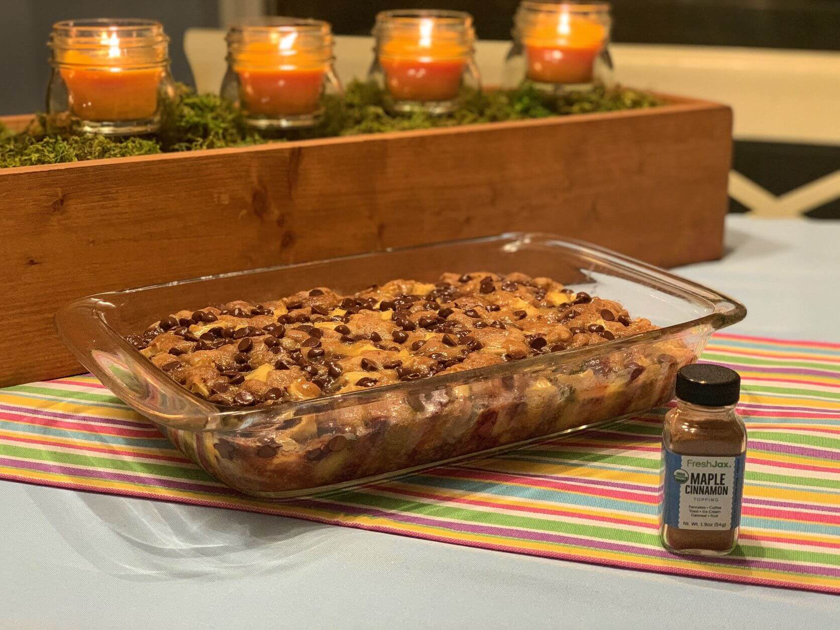 Chocolate chip apple cake in glass dish with a sampler bottle of FreshJax maple cinnamon topping. Orange candles in background.