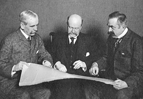 Wead, McKim and White sitting together holding a large paper and looking at it together.