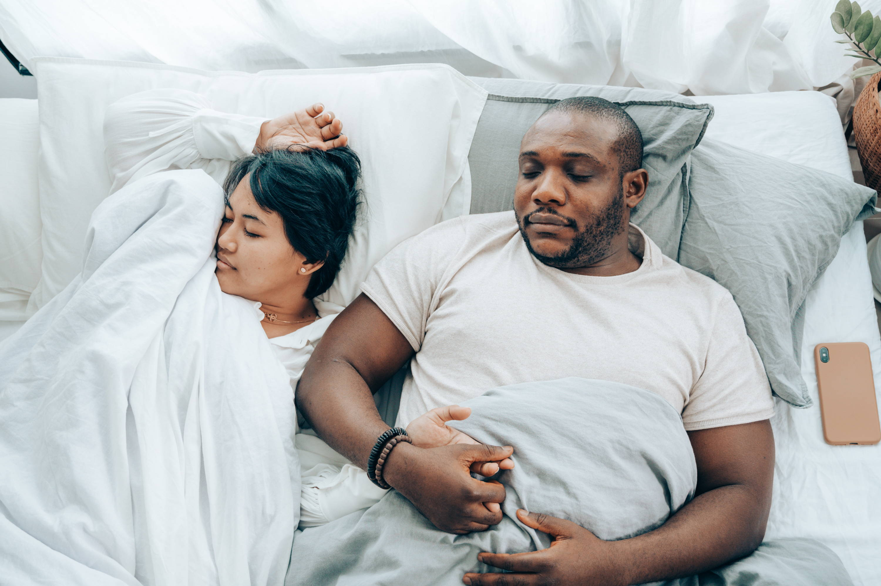 16. Young multiethnic spouses sleeping in bed holding hands - Photo by Ketut Subiyanto from Pexels