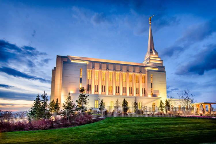 Rexburg Temple glowing against an evening sky.