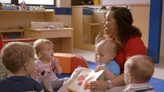 Primrose teacher reads aloud with toddlers, focusing on her pronunciations