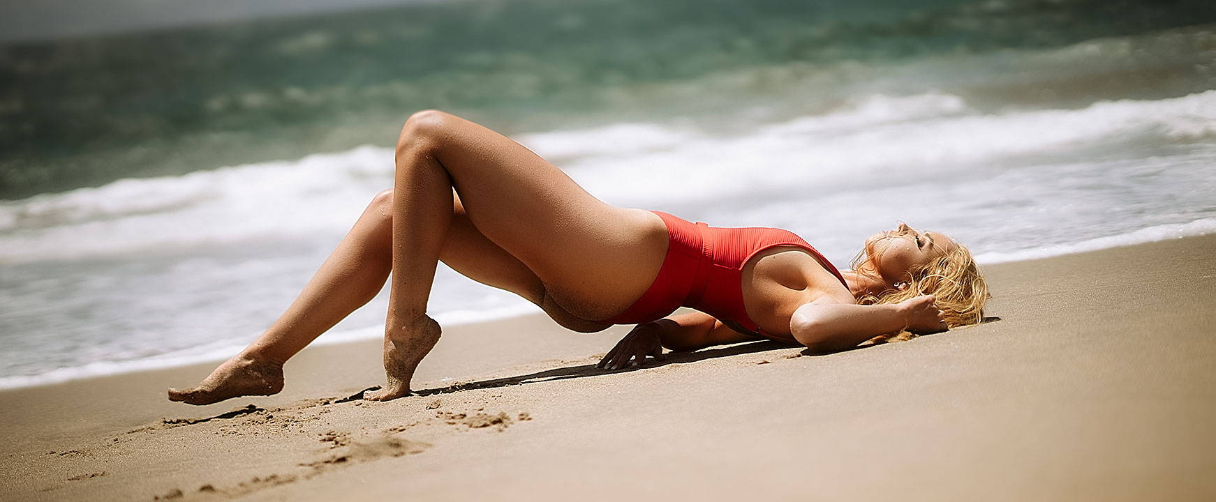 lying on the beach sand in a red belted swimsuit