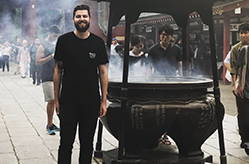 Adam is in front of a giant pot smiling and wearing a Smog City pocket t.