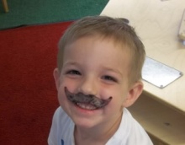 Little boy with a fake mustache looks up and smiles