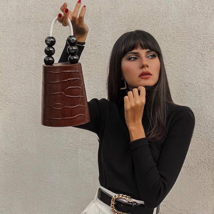 a woman is holding a bag
