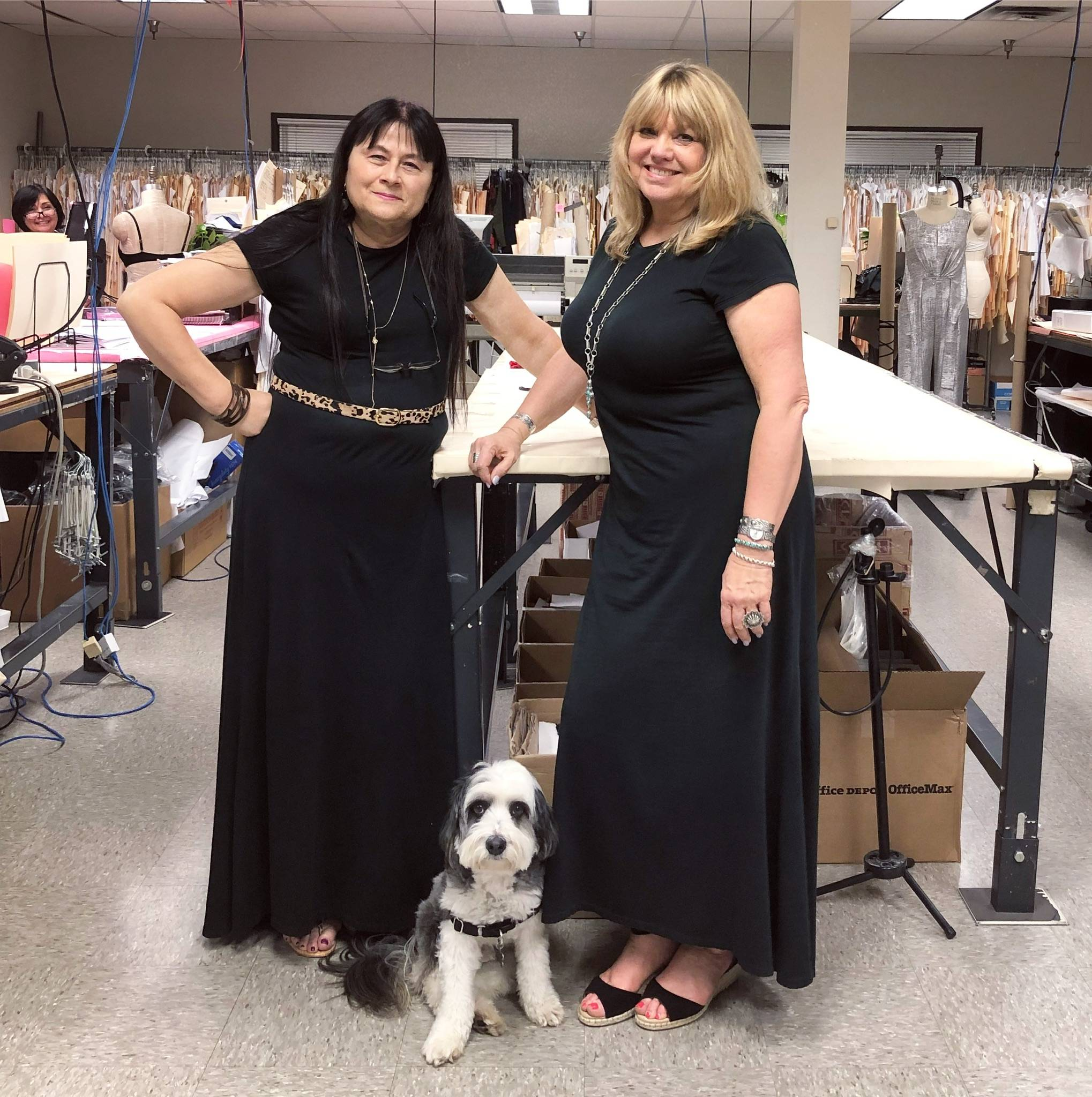 two women in matching black outfits posing in a connected apparel pattern room
