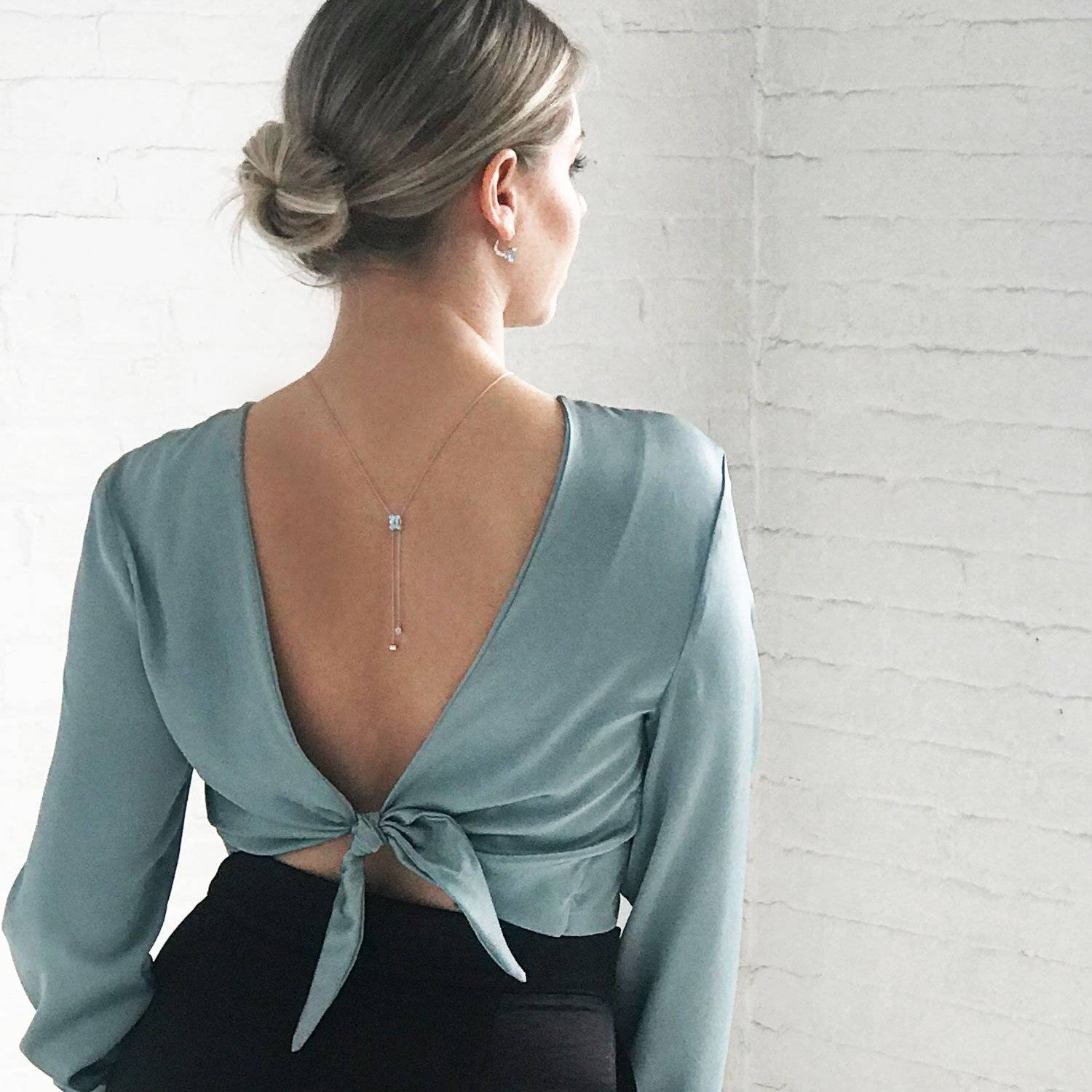 A beautiful woman staring out a window wearing a K8 Jewelry lariat necklace as a back lace. The blouse with V back is the same color as the large aquamarine in the necklace.  Edit alt text