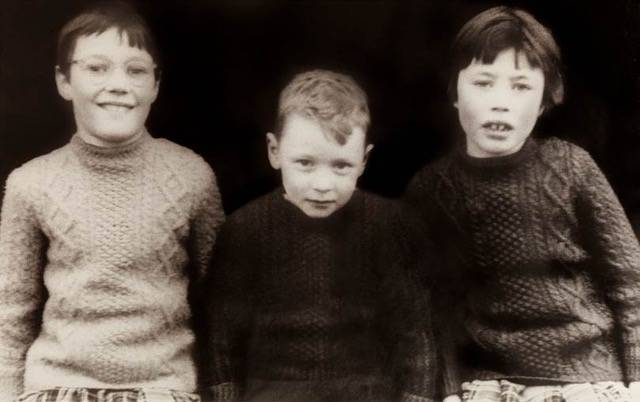 School photo of Margaret O'Leary at age nine, along with two siblings. Wearing traditional Irish sweaters knit by her mother.