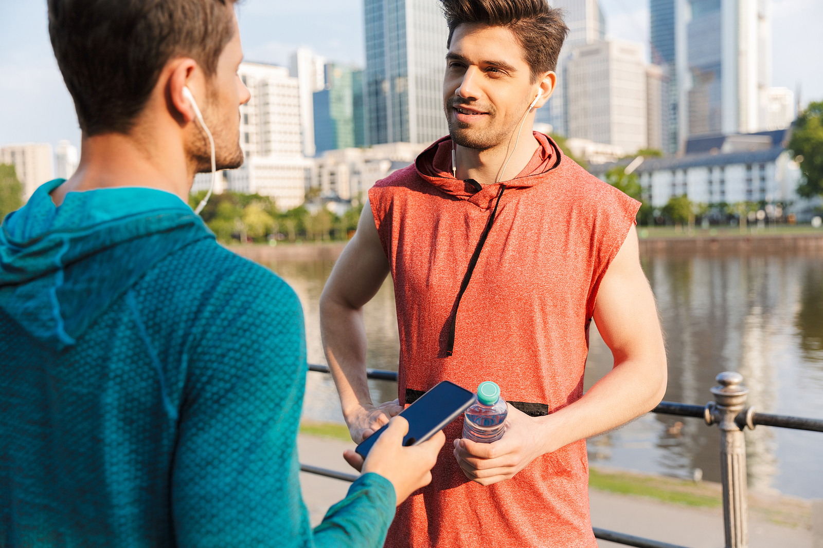 Photo of 2 young white guys with workout clothes both talking to each other near a lake in the city.