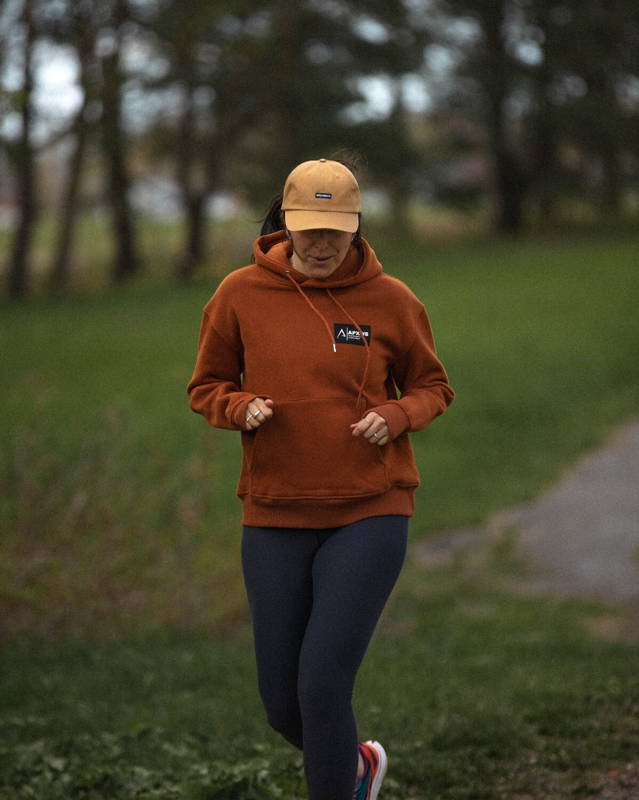 girl running outside wearing apexways orange hoodie