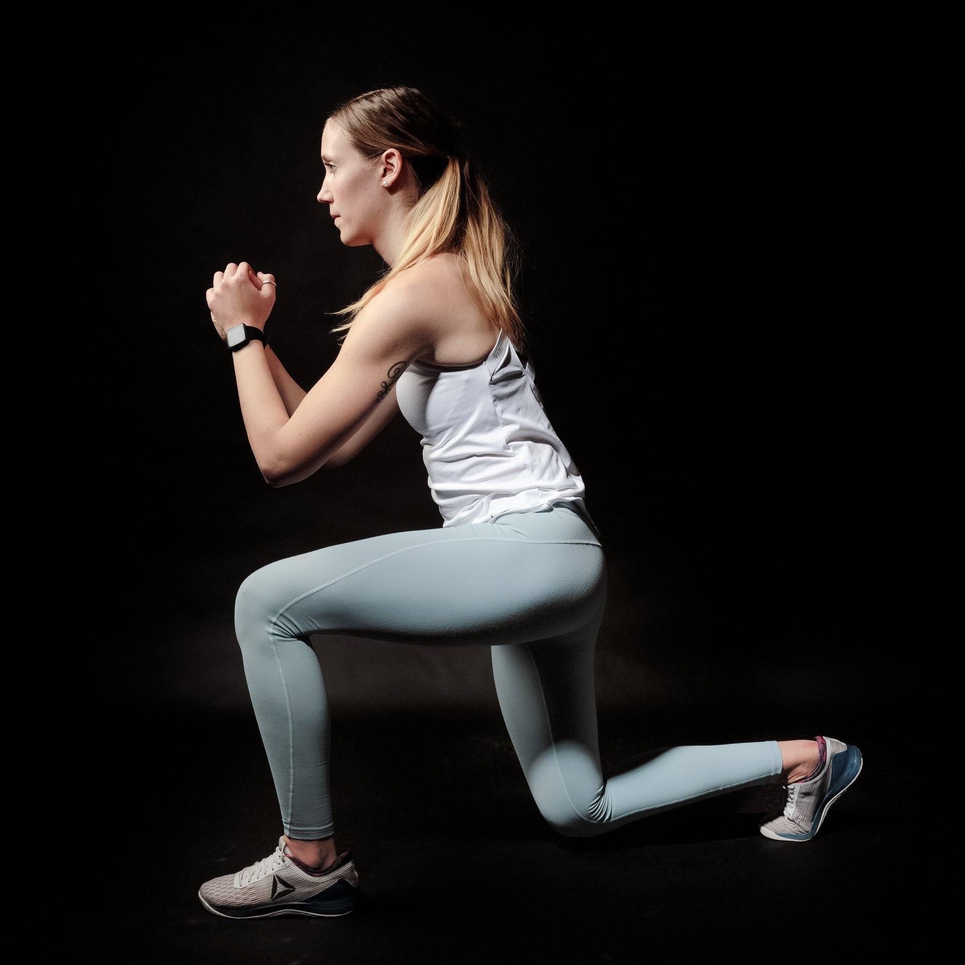 Female runner doing lunges in the dark