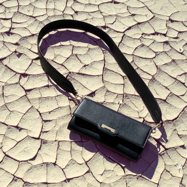 Black vegan leather crossbody mini handbag wallet styled in the desert of California