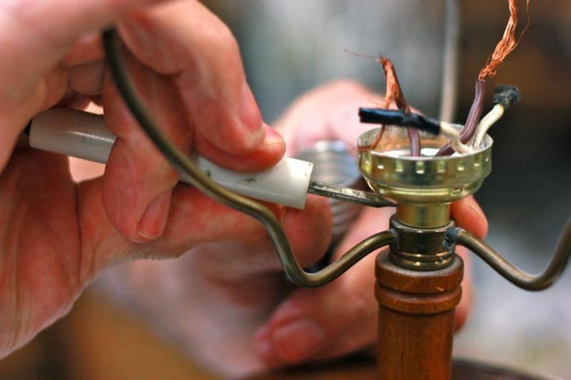 picture of man repairing a broken lamp.