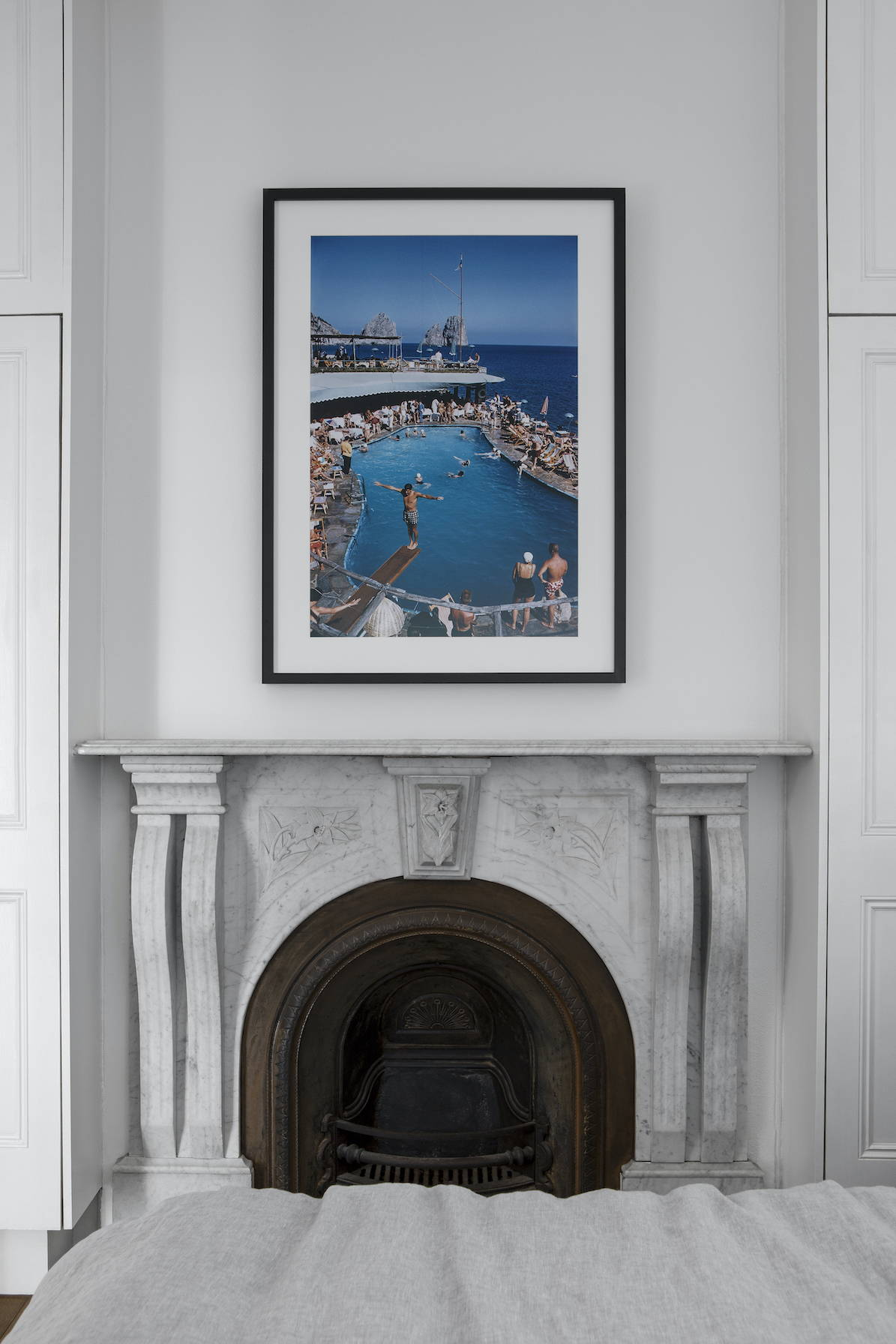 A bright blue ocean and pool scene captured by vintage photographer Slim Aarons, framed in black in a bedroom