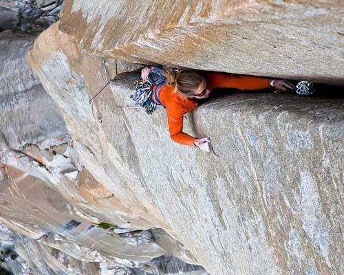 Woman wearing Patagonia sustainable climbing clothing in a crack in Yosemite