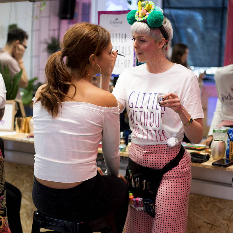 Photo shows a women having her makeup done by a professional glitter artist at an EcoStardust glitter bar for hire
