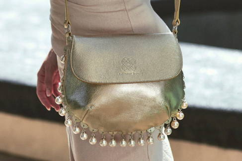 Close up view of CHARMAINE gold leather shoulder bag with  hanging pearl charms, worn on the shoulder.