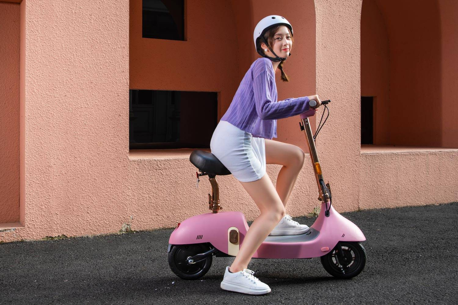 okai ea10 electric scooter girl riding with helmet