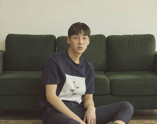an asian man sits on the floor