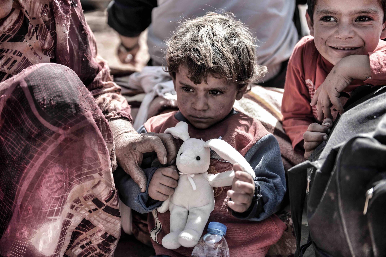Syrian refugee boy clutching a teddy