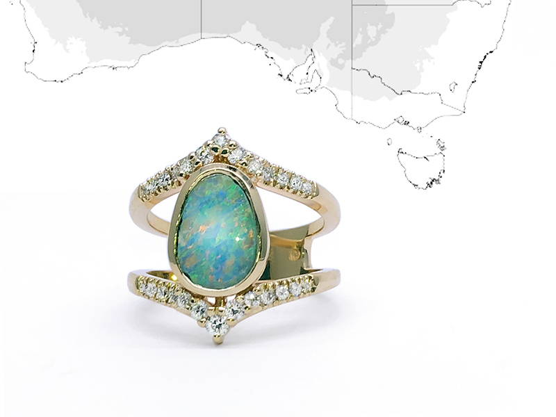 Australian Opal set on a princess ring with about twenty small diamonds anchored on the yellow gold ring body.