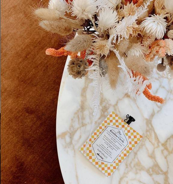 A Davines hair mask sitting on a marble table with flowers