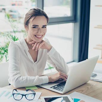 Frau sitzt am Laptop auf ergonomischem Sitzkissen