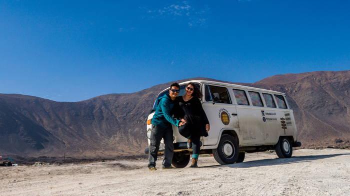 casal de viajantes em frente a kombi usada na viagem, cenário de montanhas na costa do Chile