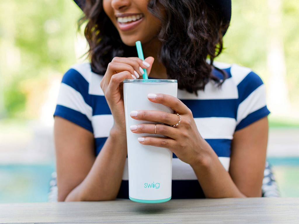 Women outside smiling while drinking beverage out of cup with reusable straw