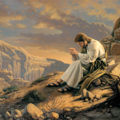 Jesus sitting in the desert, hands clapsed and head bowed in prayer.