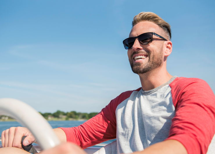 Man with restored hair driving boat.