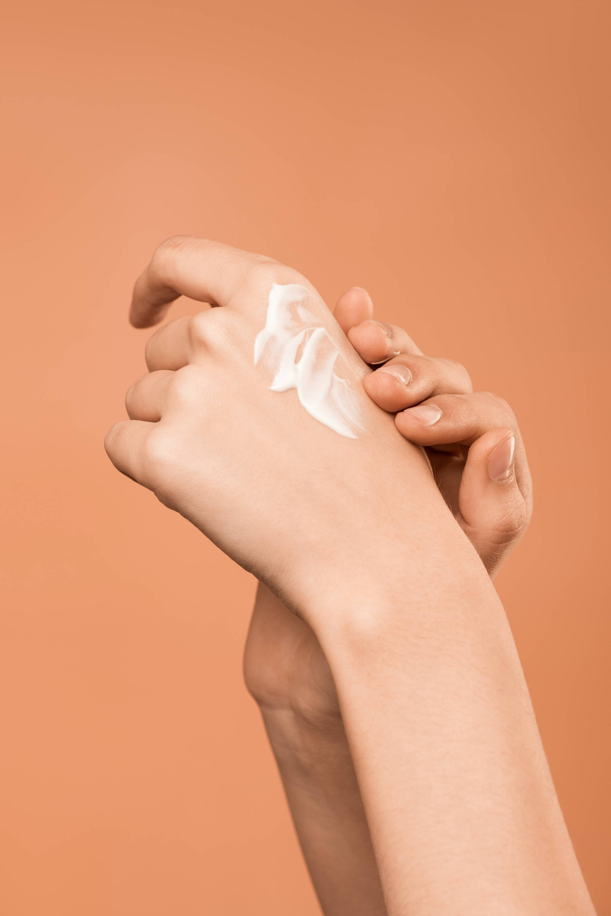 moisturizer on a pair of hands with a pink, peach background