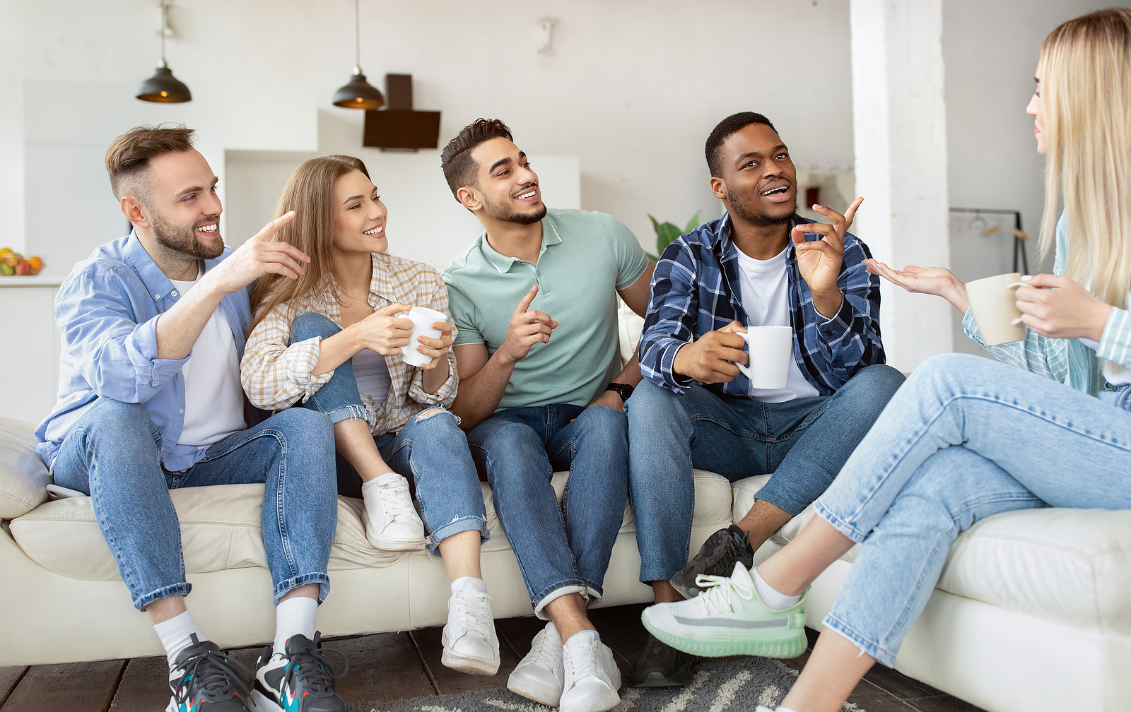 Image of several friends of different ethnicities sitting on a couch together with their coffee mugs asking questions to the blond haired woman on the right.