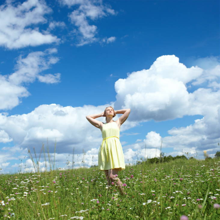 woman wearing yellow dress in a green field of grass on a cloudy blue sky day