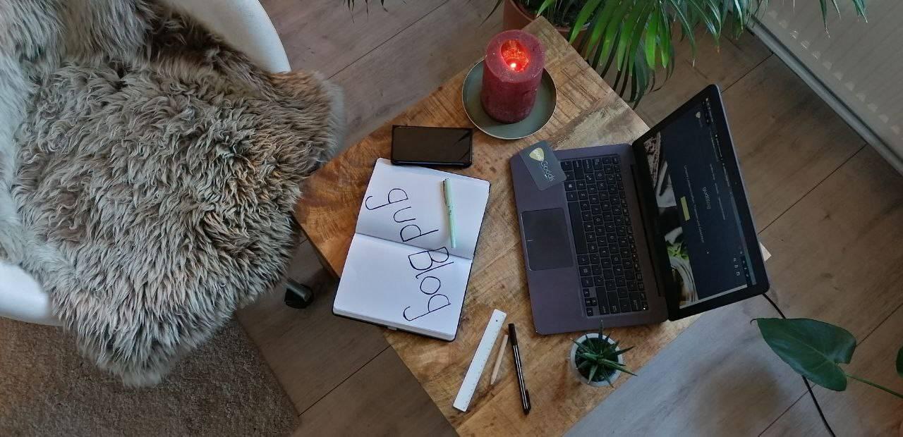 Buch, Stifte, Laptop, Pflanze, Handy und Kerze auf Holztisch