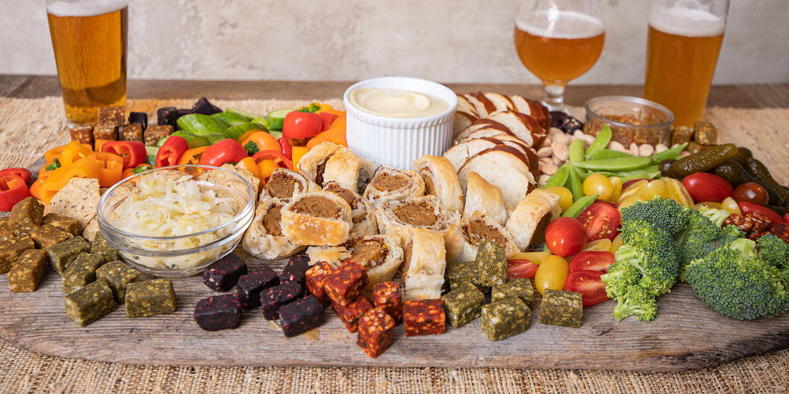 Vegan grazing board with vegetables, vegan cheese, and plant-based meat, paired with beers.
