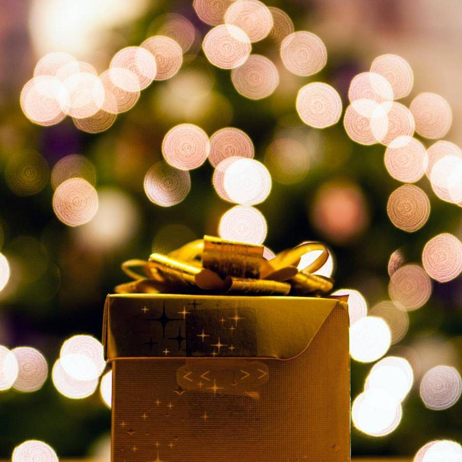 gold gift box with Christmas lights in background
