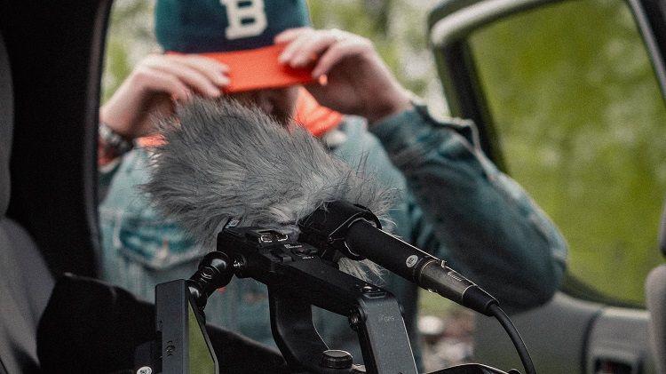 A filmmaker get their equipment out of a car.