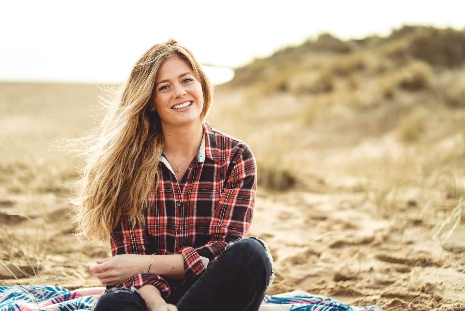 Image of abi sitting on beach with natural wavy hair
