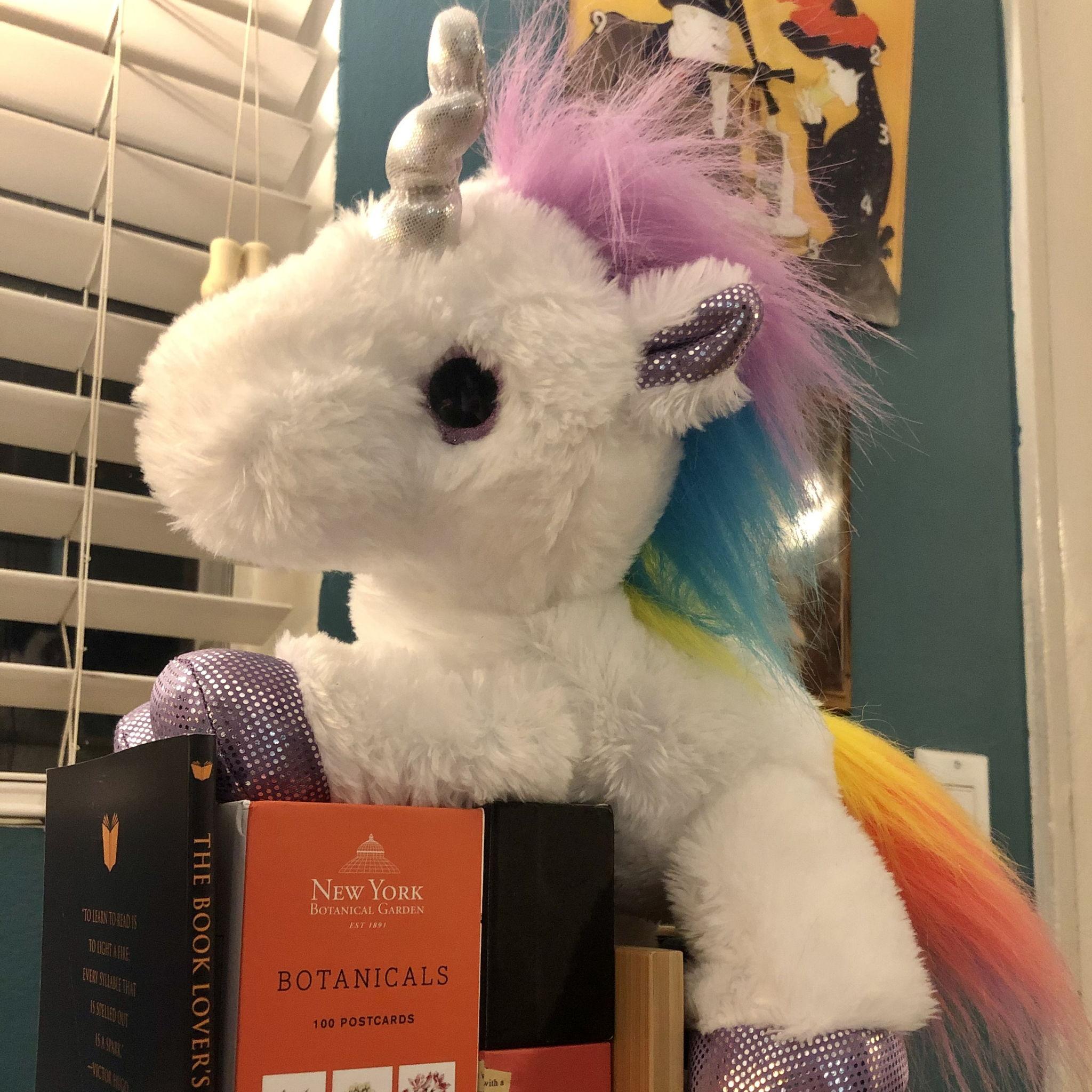 A plush Unicorn sitting on a pile of books.