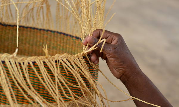 Hands on detail of Bolga basket weaving and african moses baskets