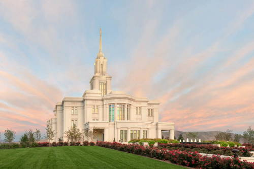 Photo of the Payson Utah Temple against pink clouds and a blue sky.