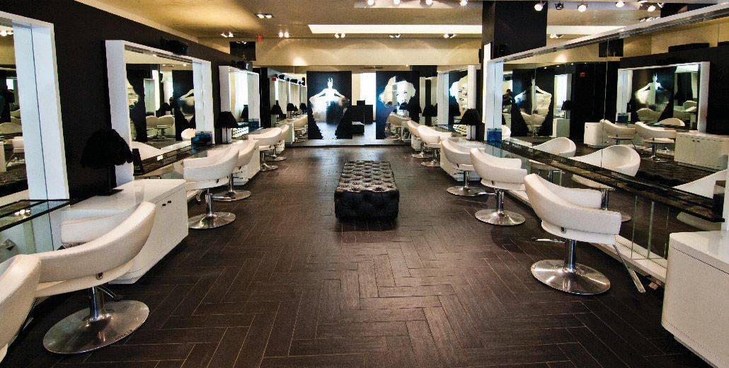 Warren Tricomi's Greenwich, CT location with black tile floors, white salon chairs, and wall mirrors