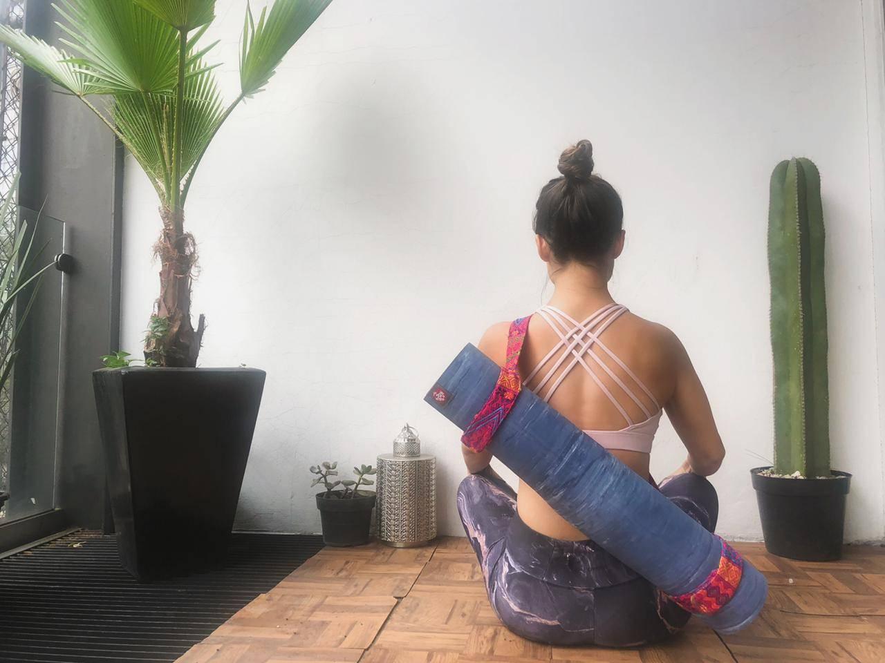 woman sitting with yoga matt on her back