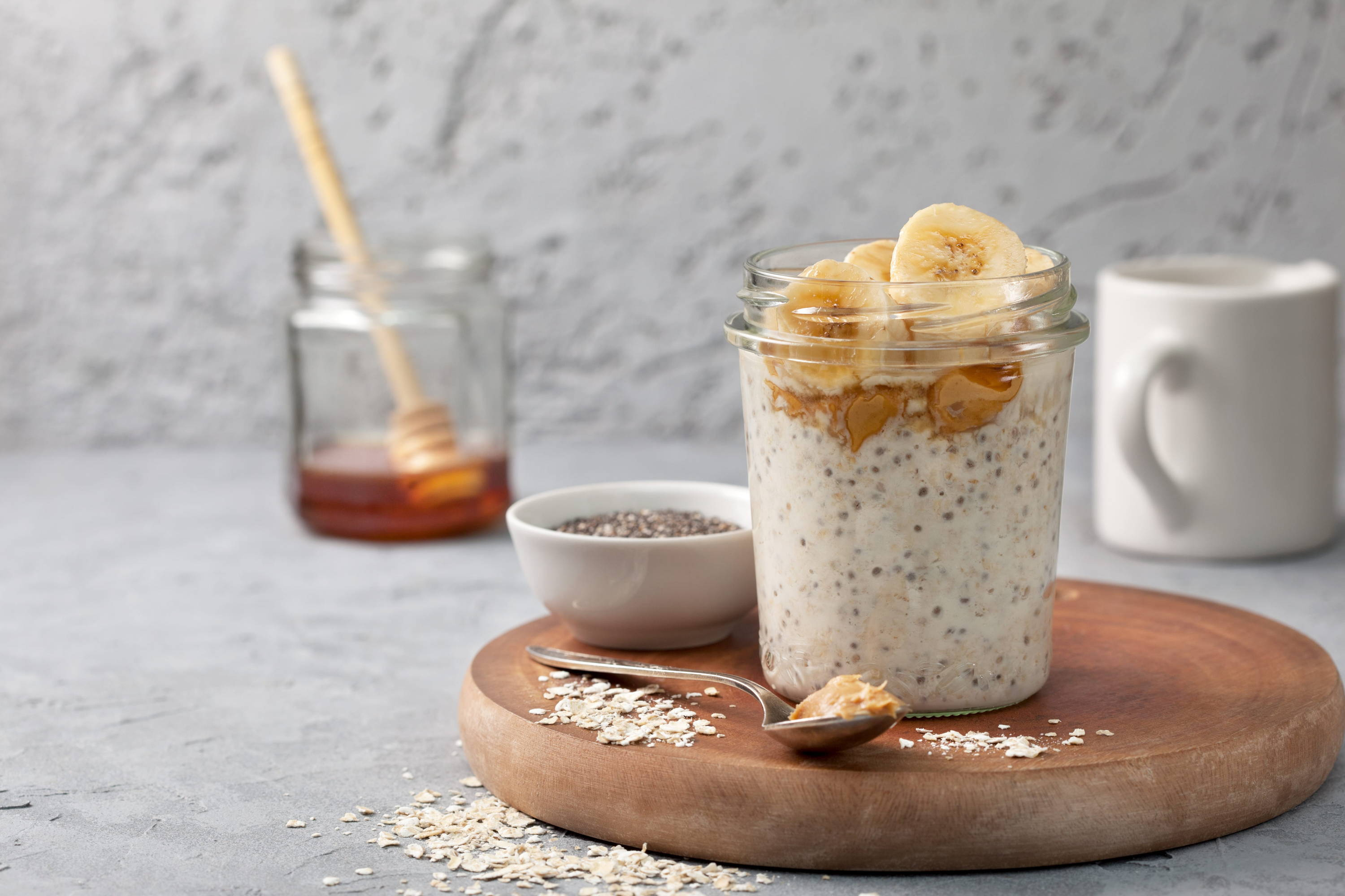 Healthy overnight oats in a glass jar with milk, honey, chia seeds and bananas to help build collagen