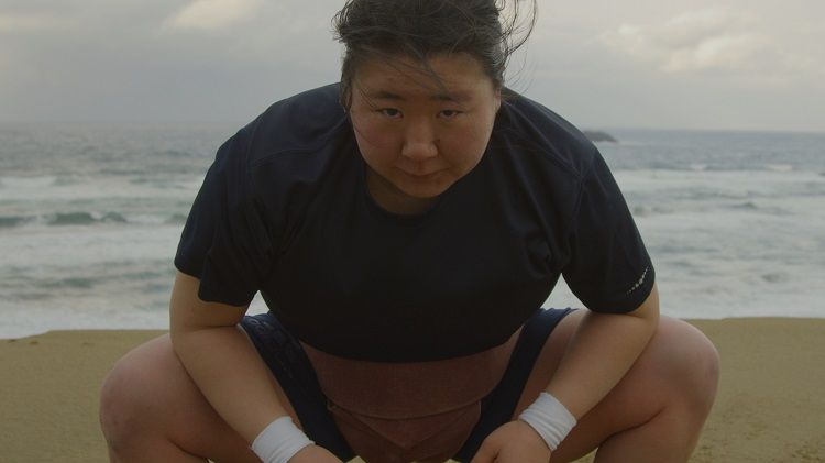 A young female Sumo wrestler on the beach with the sea behind her.