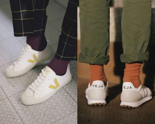Vegan sneakers from Veja with man wearing white trainers with orange socks and green chinos and woman wearing sustainable Veja white pumps with purple socks and navy yellow checked trousers