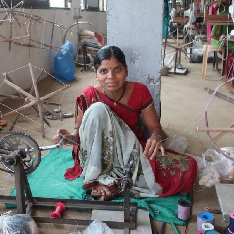 woman in red sari spinning yarn in india